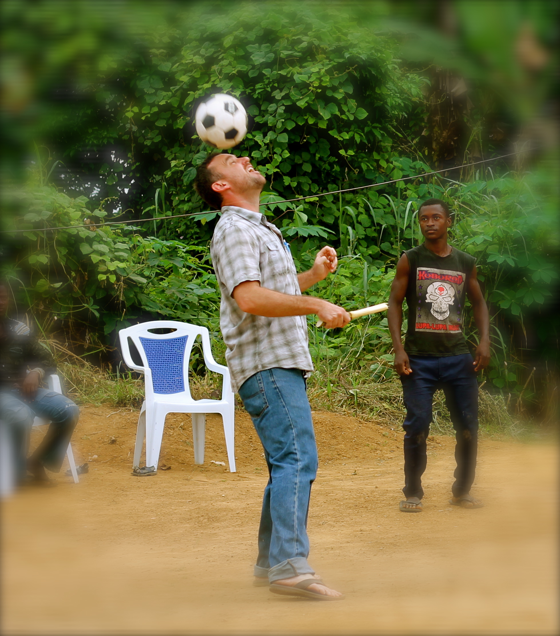 Tim playing soccer in village